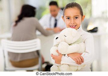 little girl with teddy bear in pediatrician office
