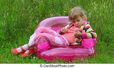 little girl with telephone lying on inflatable armchair