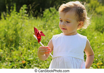 Little girl with the red pinwheel standing in the grass and looking at the pinwheel