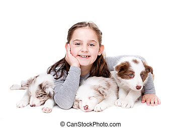 little girl with three border collie puppy dogs