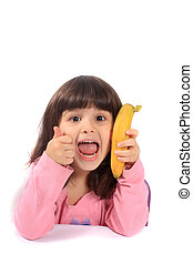 Little girl with thumbs up for banana
