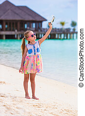 Little girl with toy airplane in hands on white sandy beach