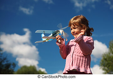 little girl with toy airplane in hands outdoor against sky