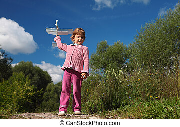 little girl with toy airplane in hands outdoor full body