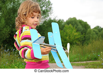 little girl with toy airplane in hands outdoor