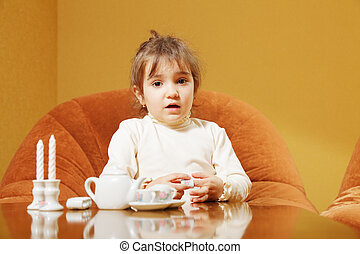 Little girl with toy dishware