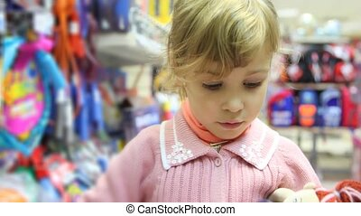 little girl with toy in shop