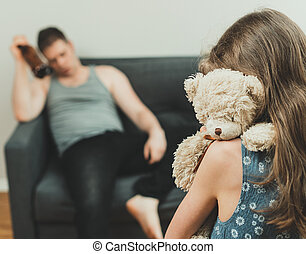 Little girl with toy standing in front of her drunk father.