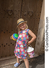 Little Girl with Toys Posing Infront of Wooden Doors
