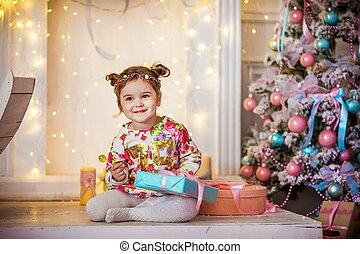 Little girl with two pigtails on the background of a Christmas tree with a gift in her hands
