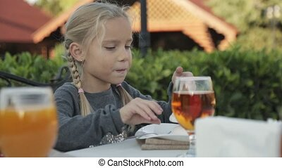 Little girl with two plaits sitting at the table in the outdoor cafe