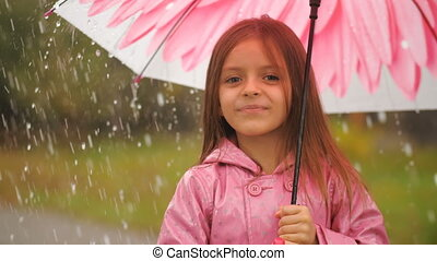 Little girl with umbrella under rain