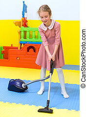 Little girl with vacuum cleaner in playroom.