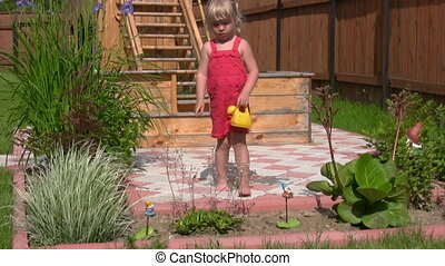 little girl with watering can pouring on flowers in garden