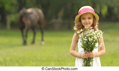 Little girl with wild flowers in their hands sniffs them. Slow motion