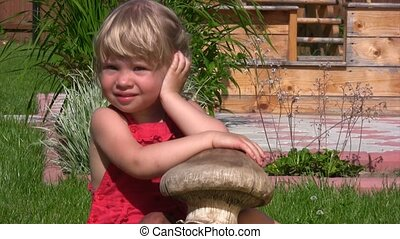 little girl with wooden fungi on grass