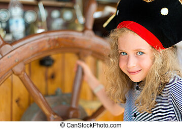 Little girl with wooden ship's wheel.