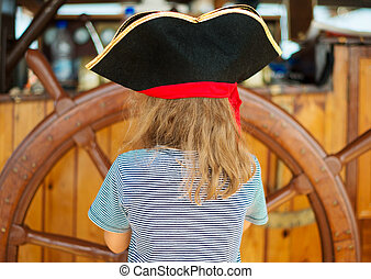 Little girl with wooden ship's wheel. From the back.