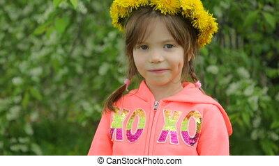 Little girl with wreath of dandelion