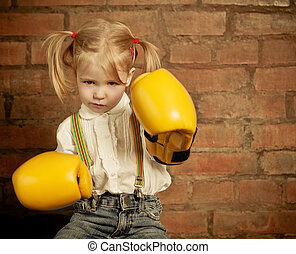 Little girl with yellow boxing gloves over brick wall...