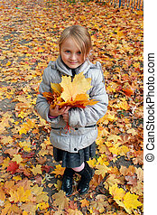 little girl with yellow leaves in the park
