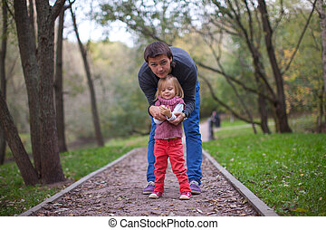 Little girl with young dad in the park at warm autumn day