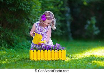 Little girl working in the garden watering flowers - Child...