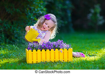 Little girl working in the garden watering flowers - Child...