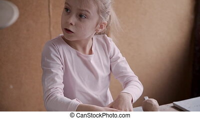 Little girl working with clay in pottery workshop studio