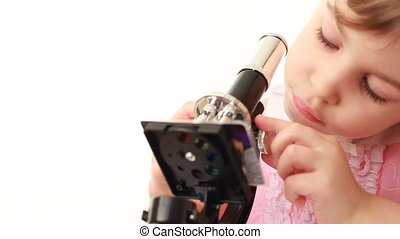 Little girl works with microscope making some research