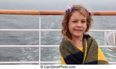 Little girl wrapped in plaid stands on deck during cruise -...