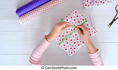 Little girl wrapping gifts for holidays