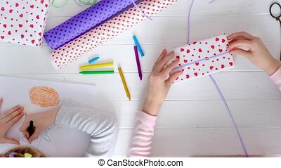 Little girl wrapping gifts for holidays - Little girls...