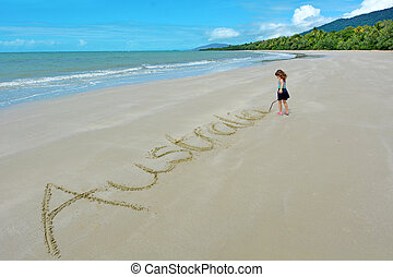 Little girl write the word Australia in the sand