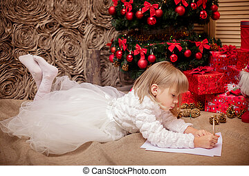 little girl writes a letter to Santa Claus near Christmas ...
