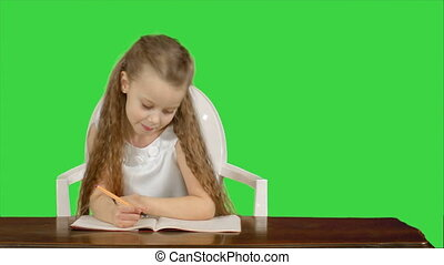 Little girl writes to writing-book on a Green Screen, Chroma Key