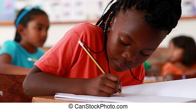 Little girl writing and smiling at camera during class in ...
