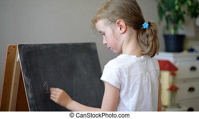 Little girl writing on blackboad.
