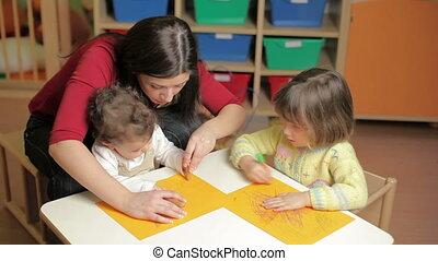 female teacher, toddler and 2-3 year girl drawing in kindergarten