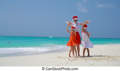 Little girls and young mother in Santa Hats on beach Christmas vacation