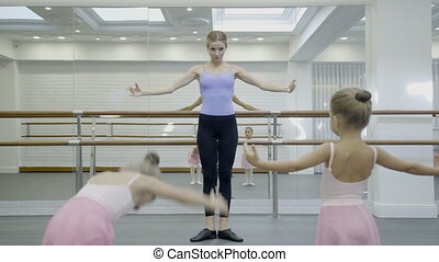 Little girls are practice with teacher in ballet school indoors.