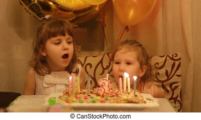 Little girls blows out candles on birthday cake at party. Funny happy kids. The concept of a children's holiday. 3 years.
