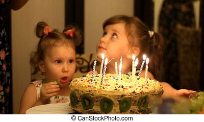 Little girls blows out candles on birthday cake at party. Funny happy kids. The concept of a children's holiday