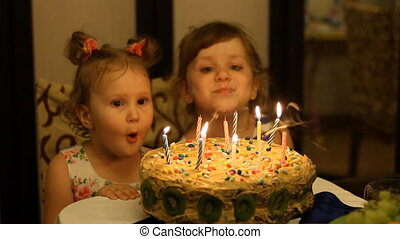 Little girls blows out candles on birthday cake at party