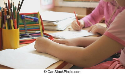 Little girls draw a pictures in the copybook