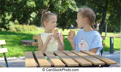 Little girls eating ice-cream outdoors at summer in outdoor cafe. Cute kids enjoying real italian gelato