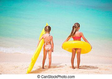 Little girls going to swim on summer beach vacation