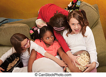 Little Girls Grab Popcorn - Little girls grab popcorn at a...