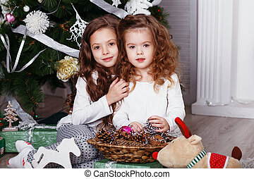 Little girls in comfortable home clothes sitting on floor in beautiful Christmas decorations