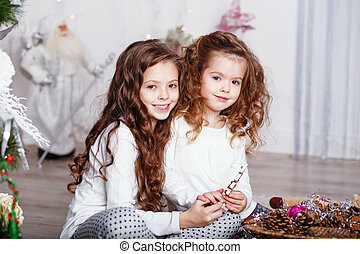 Little girls in comfortable home clothes sitting on floor in beautiful Christmas decorations.